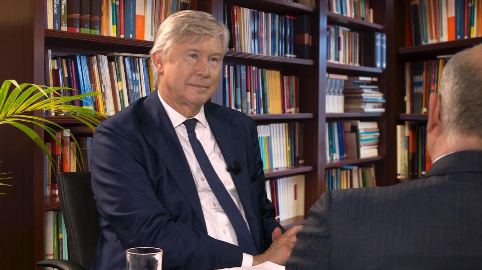prof. mr. Fons Stollenwerck voor een boekenkast tijdens een interview